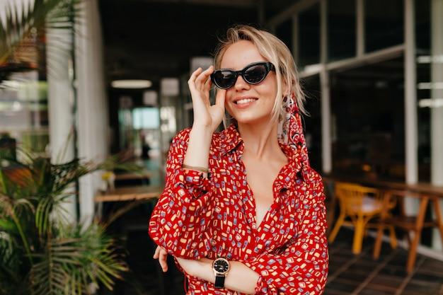 Lachende vrouw met blonde haren haar bril in zomerterras aan te raken