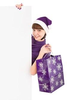 Lachende vrouw met boodschappentas in kerstmuts met leeg bord, geïsoleerd op wit