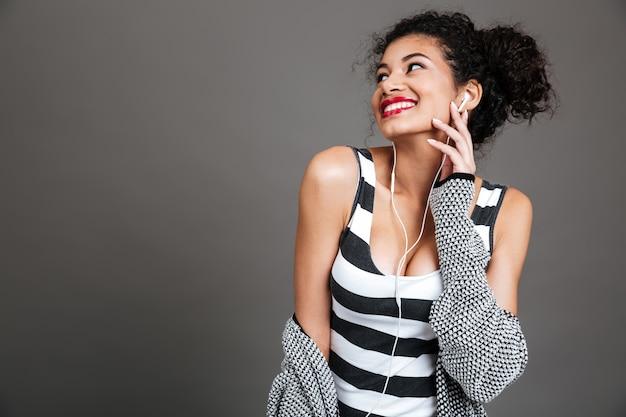 Lachende vrouw met celtelefoon en oortelefoons