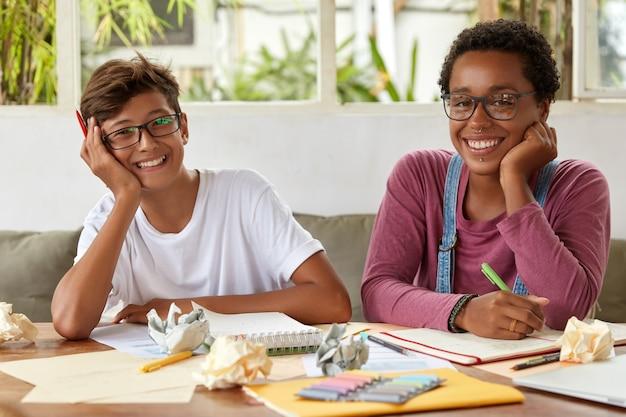 Lachende vrouw met donkere huid geeft goed advies aan mannelijke klasgenoot, praat over algemeen huiswerk, noteert records in spiraalvormig notitieboekje, praat over gemeenschappelijk project en maak samen onderzoek of plannen