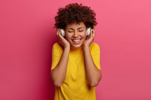 Lachende vrouw met donkere huid geniet van melodie, koptelefoon raakt