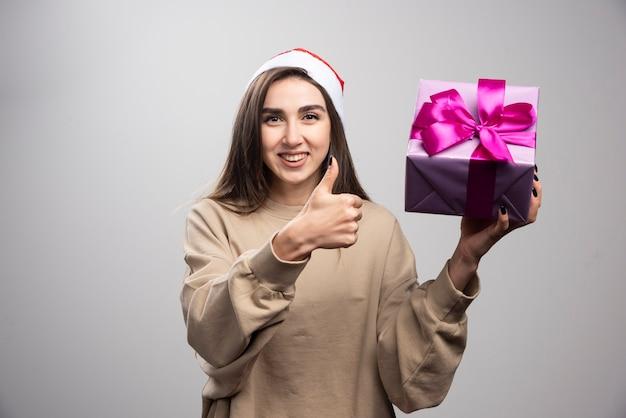 Lachende vrouw met een doos met kerstcadeautjes met een duim.