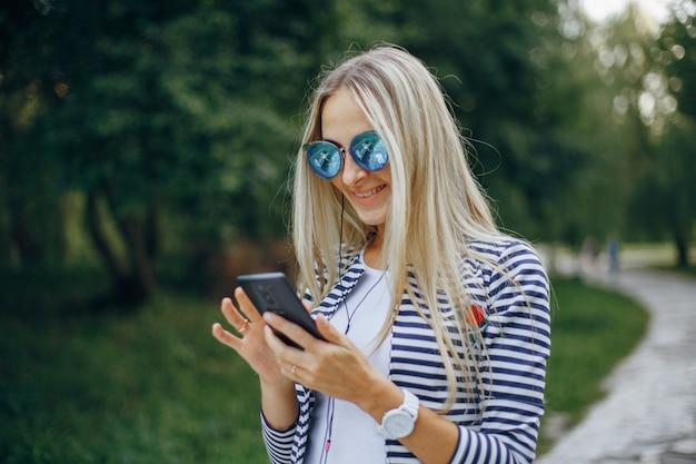 Lachende vrouw met een zonnebril te typen op een mobiel