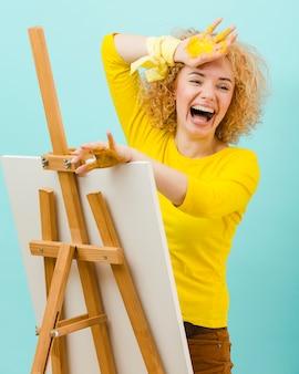 Lachende vrouw met gele verf