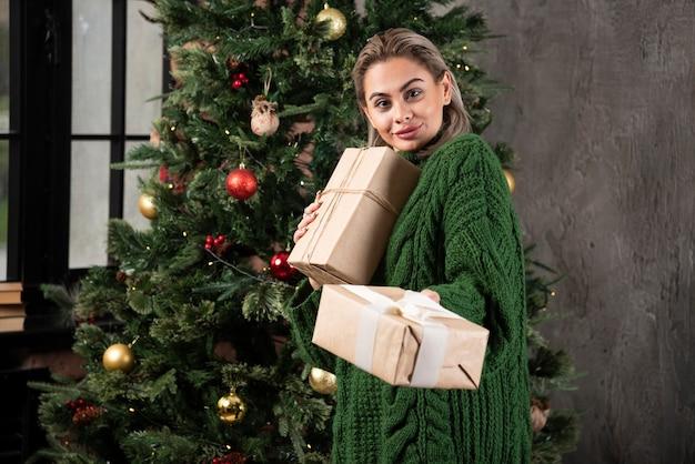 Lachende vrouw met geschenkdoos in de buurt van een kerstboom