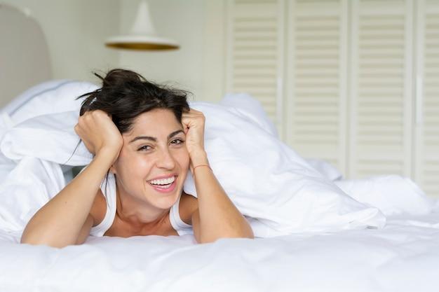 Lachende vrouw met haar handen op het voorhoofd