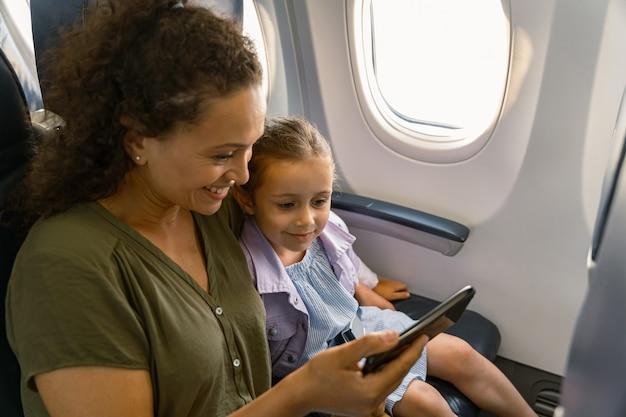 Lachende vrouw met haar kind in het vliegtuig zitten en smartphone gebruiken