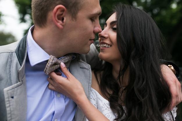 Lachende vrouw met haar linkerhand op haar man vlinderdas