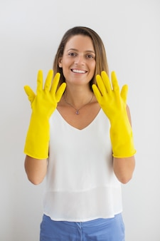 Lachende vrouw met handen in rubberen handschoenen