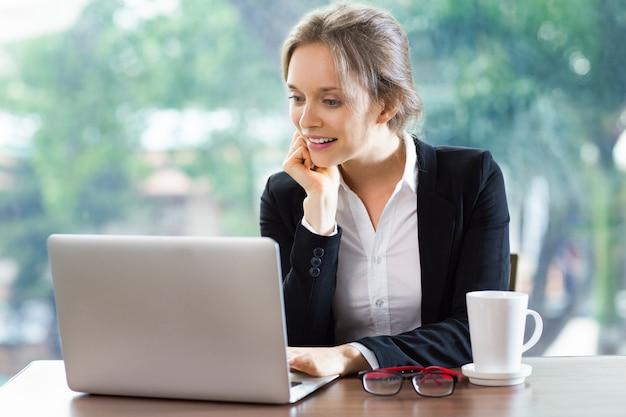 Lachende vrouw met het hoofd rustend op een hand te kijken naar een laptop