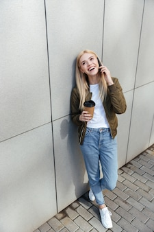 Lachende vrouw met koffie praten op smartphone