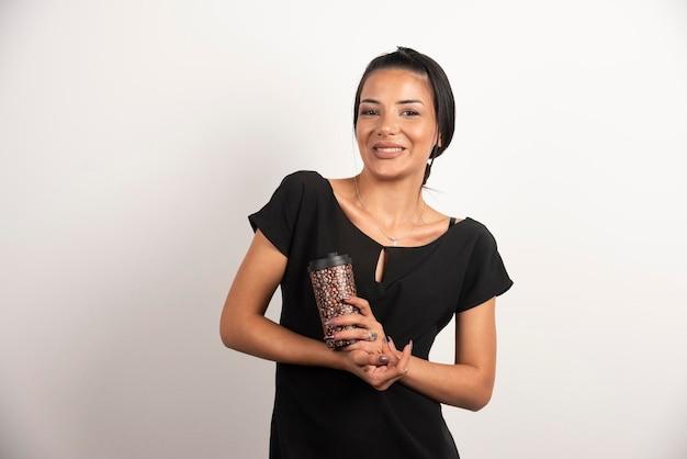 Lachende vrouw met kopje koffie poseren op witte muur.