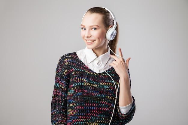 Lachende vrouw met koptelefoon luisteren naar muziek op speler en wijzend op een van de koptelefoons. muziek tiener meisje portret tegen geïsoleerde grijze achtergrond