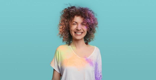 Lachende vrouw met krullend haar met holi-verf