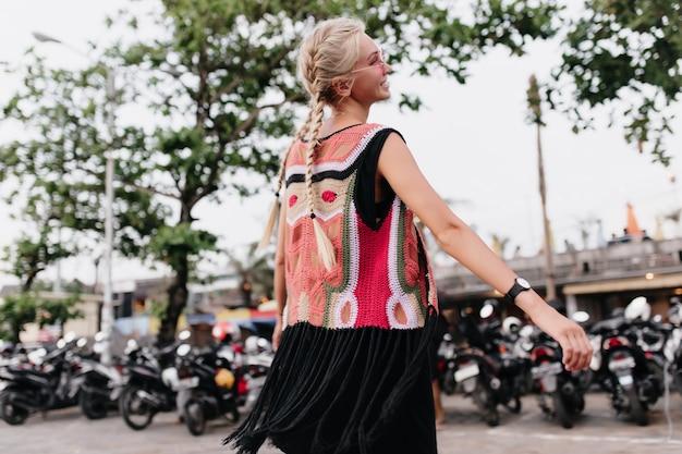Lachende vrouw met lange blonde vlechten. buiten schot van bevallige gebruinde vrouw draagt kleurrijke gebreide kleding.