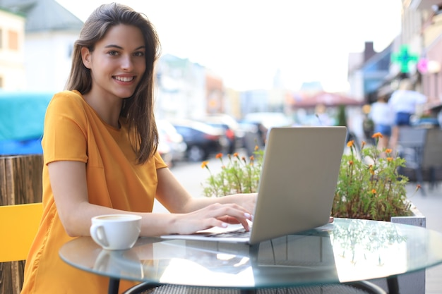 Lachende vrouw met laptop in café. concept van ondernemer, zakenvrouw, freelance werknemer.