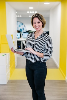 Lachende vrouw met laptop op kantoor
