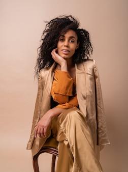 Lachende vrouw met perfect krullend haar in elegante oranje blouse en zijden broek zittend op een vintage stoel