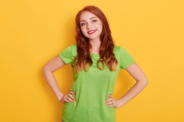 Lachende vrouw met rood haar en heldere lippen poseren geïsoleerd, hand in hand op de heupen, lachend rechtstreeks in de camera kijken