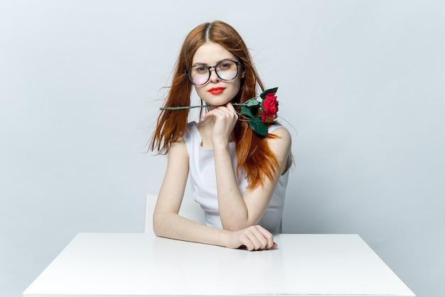Lachende vrouw met roze bloem in handen bureau emoties cadeau luxe