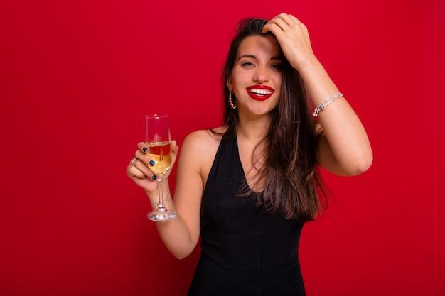 Lachende vrouw met schattige glimlach, gekleed in zwarte kleding met rode lippenstift met een glas champagne poseren over rode muur