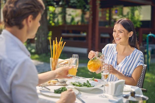 Lachende vrouw met sinaasappellimonade in de hand terwijl ze naar de man aan tafel in restaurant kijkt
