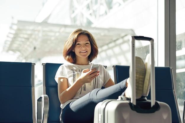 Lachende vrouw met ticket en bagage in de luchthaven. het concept van de luchtreis met jonge toevallige meisjeszitting met handbagagekoffer bij poort die in terminal wachten.