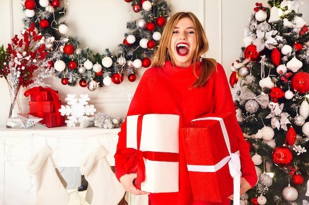 Lachende vrouw met veel geschenkdozen poseren in de buurt van versierde kerstboom Gratis Foto