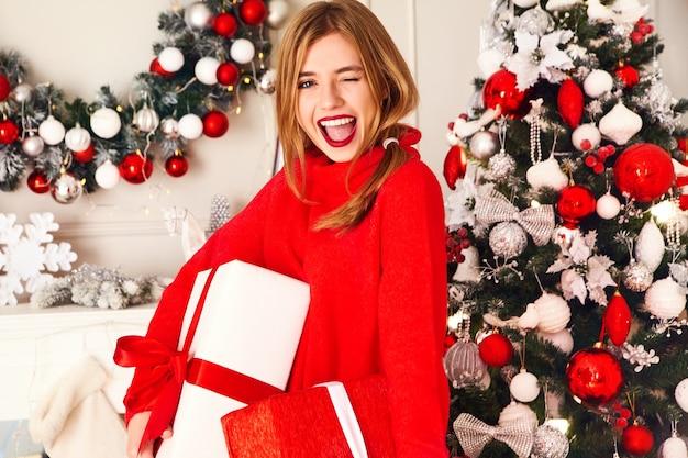 Lachende vrouw met veel geschenkdozen poseren in de buurt van versierde kerstboom