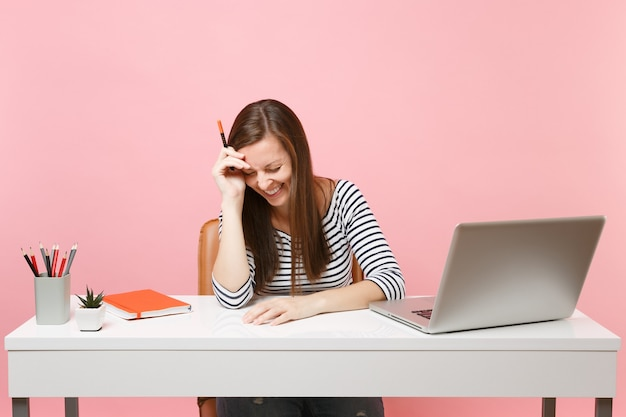 Lachende vrouw met verlaagd hoofd met potlood dat op de hand leunt, zit, werkt aan een wit bureau met een moderne pc-laptop