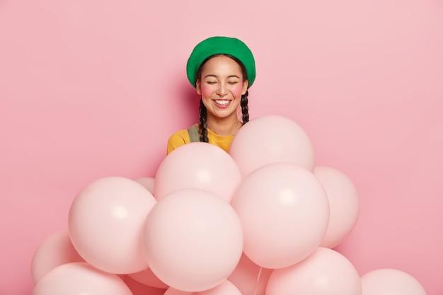 Lachende vrouw met vrolijke uitdrukking, ogen gesloten van plezier, draagt groene baret, staat met opgeblazen helium ballonnen