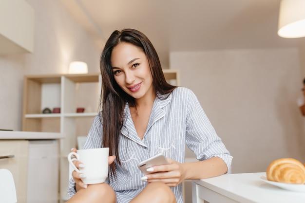 Lachende vrouw met zwart haar zittend in de keuken met smartphone tijdens het ontbijt