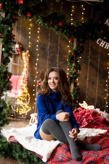 Lachende vrouw model zittend op wit laken bed met kerstversiering