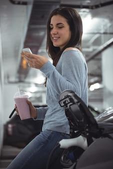 Lachende vrouw naast een auto en met behulp van mobiele telefoon