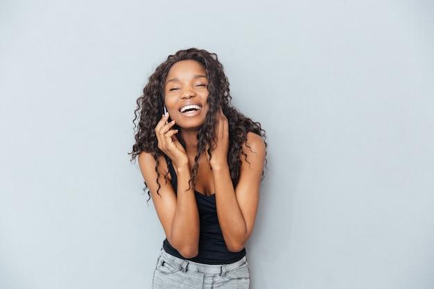 Lachende vrouw over grijze muur