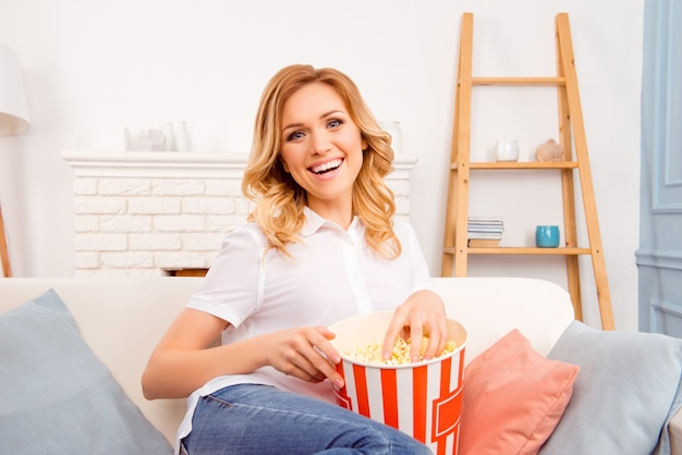 Lachende vrouw popcorn eten en kijken naar interessante komedie