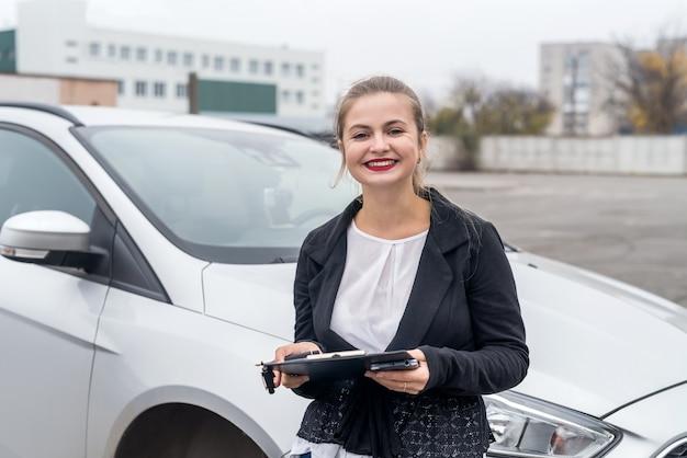 Lachende vrouw poseren in de buurt van auto met klembord