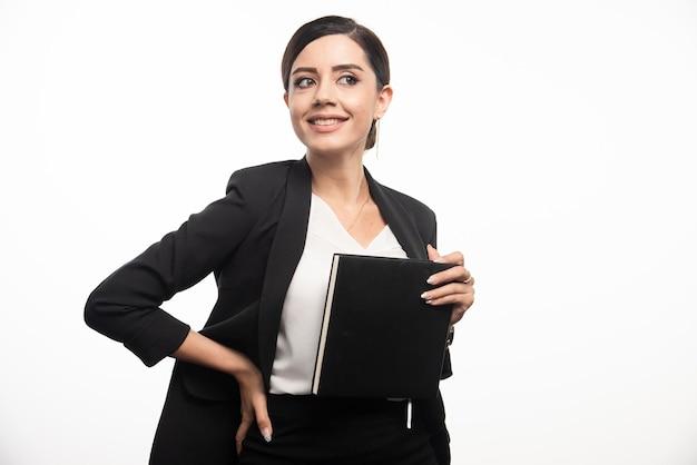 Lachende vrouw poseren met notebook op witte achtergrond. hoge kwaliteit foto