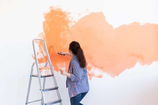 Lachende vrouw schilderij binnenmuur van huis. renovatie, reparatie en herinrichting concept.