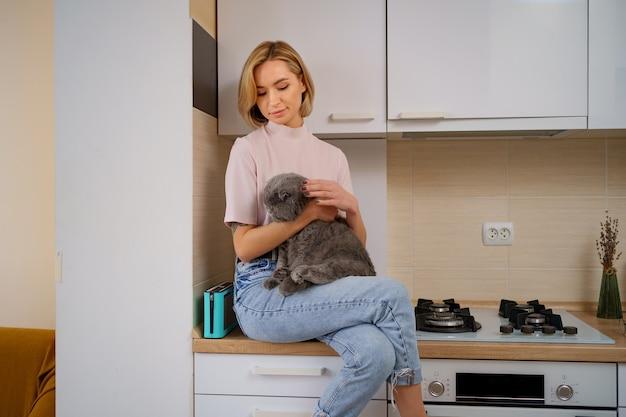 Lachende vrouw spelen met kat in de keuken thuis.