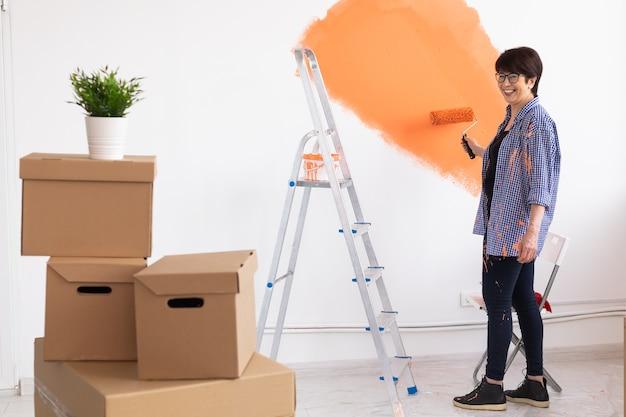 Lachende vrouw van middelbare leeftijd schilderij binnenmuur van huis. renovatie, reparatie en herinrichting