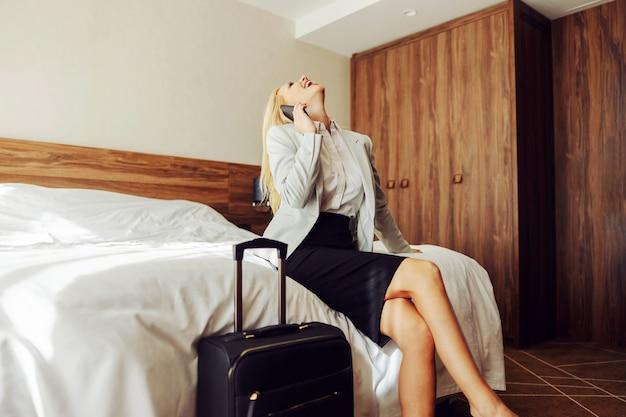 Lachende vrouw van middelbare leeftijd zittend op het bed in een hotelkamer en een telefoongesprek hebben met iemand. naast haar staat een koffer.