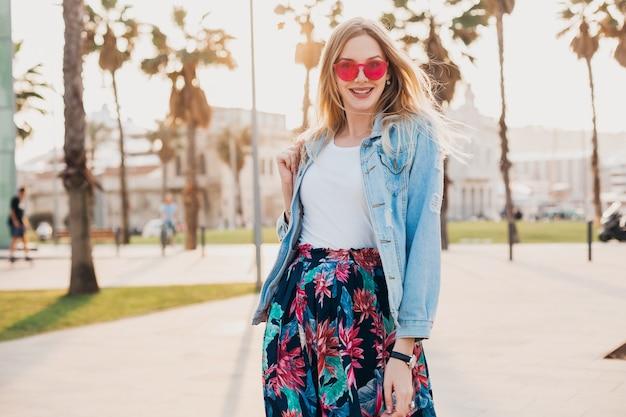 Lachende vrouw wandelen in de stad straat in stijlvolle bedrukte rok en oversized denim jasje roze zonnebril dragen