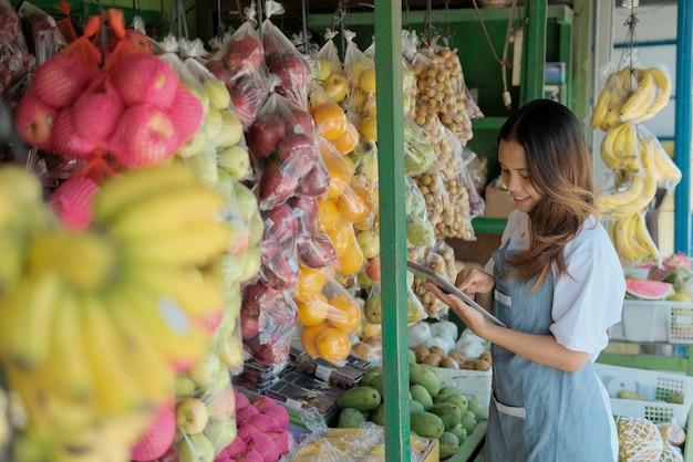 Lachende vrouw winkelbediende in schort staande met behulp van tablet