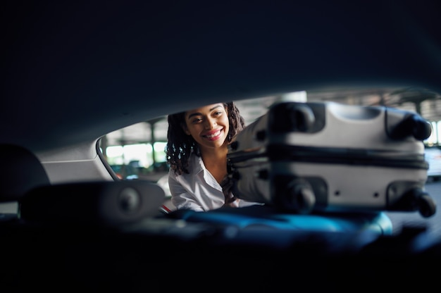 Lachende vrouw zet koffers in de auto op parking. vrouwelijke reiziger pakt bagage, parkeerterrein, passagier met veel tassen. meisje met bagage dichtbij auto