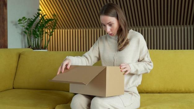 Lachende vrouw zit op de bank thuis open kartonnen leveringspakket online winkelen