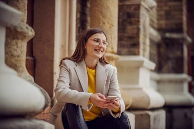 Lachende vrouw zittend op de trap bij de ingang van een oud gebouw en met behulp van slimme telefoon