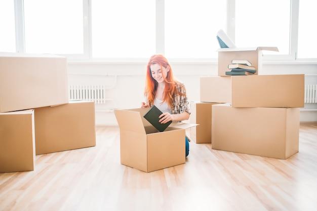 Lachende vrouw zittend op de vloer onder kartonnen dozen, housewarming. verhuizing naar nieuw huis