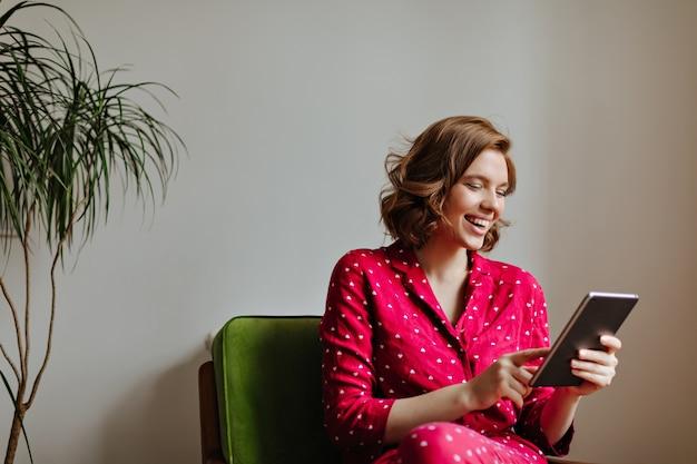 Lachende vrouw zittend op een stoel en met behulp van digitale tablet. binnen schot van mooie vrouw in pyjama gadget houden en glimlachen.