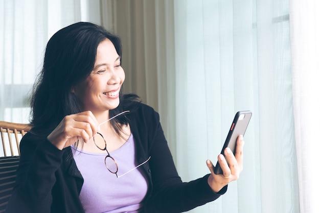 Lachende vrouw zwart lang haar vergadering holding smartphone en communiceren met familie